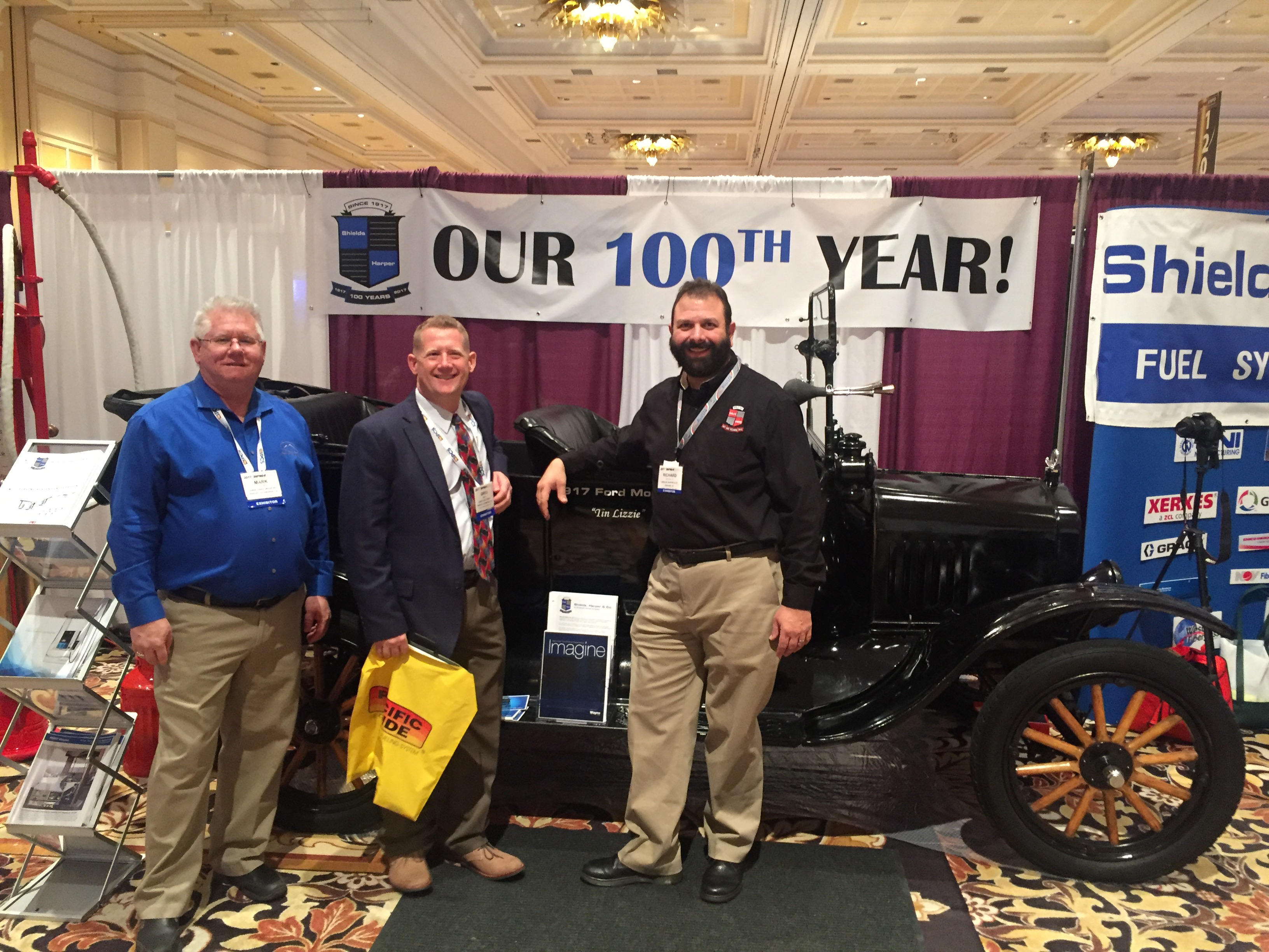 Shields, Harper & Co WPMA Booth with Richard Iacovelli and customers standing next to 1917 Ford Model T Tin Lizzie