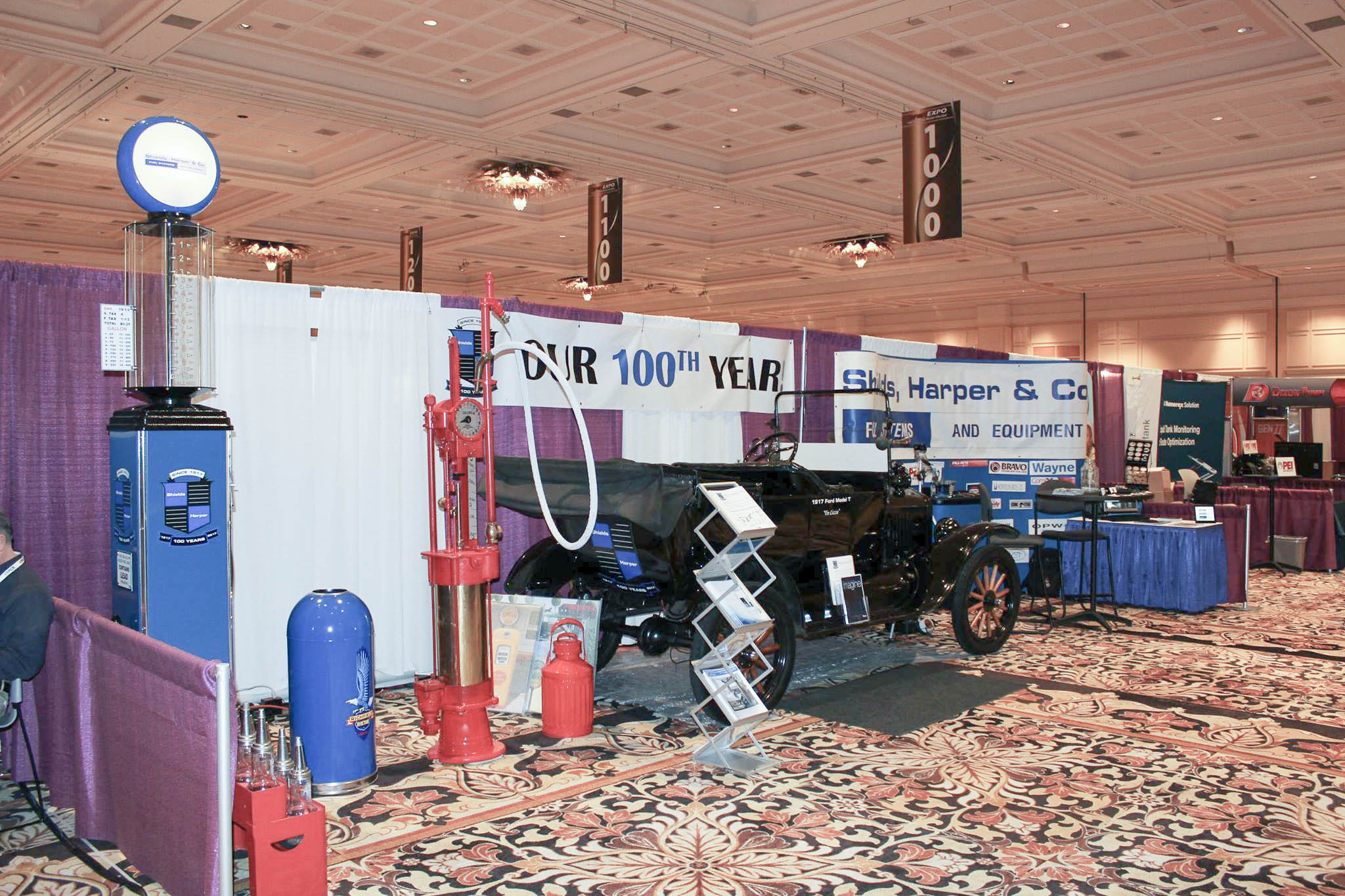 Shields, Harper & Co. WPMA Booth with visible gas dispenser and replica wayne pump and richfield trashcan